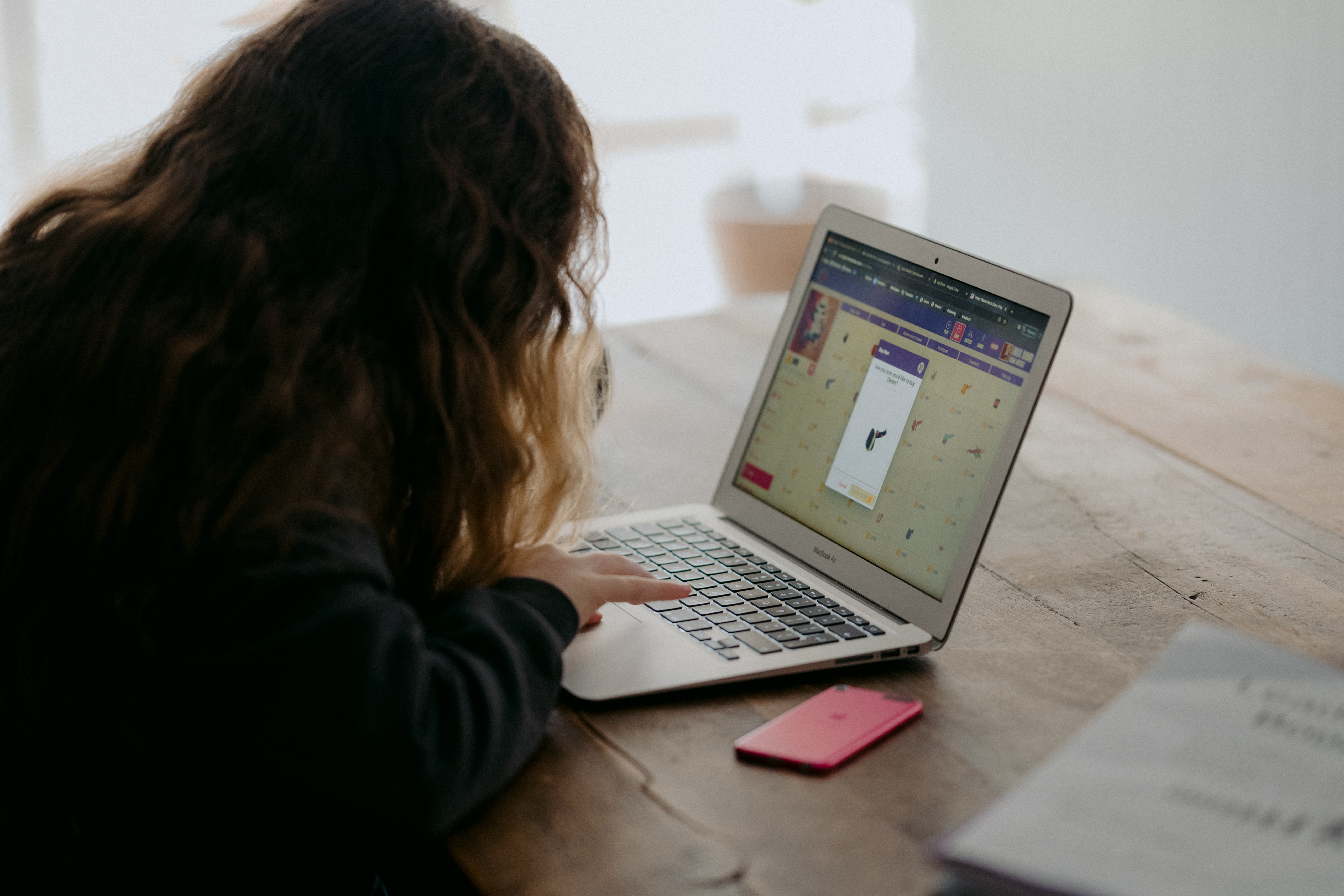 Young girl working on a laptop at a table with an iPhone and book nearby